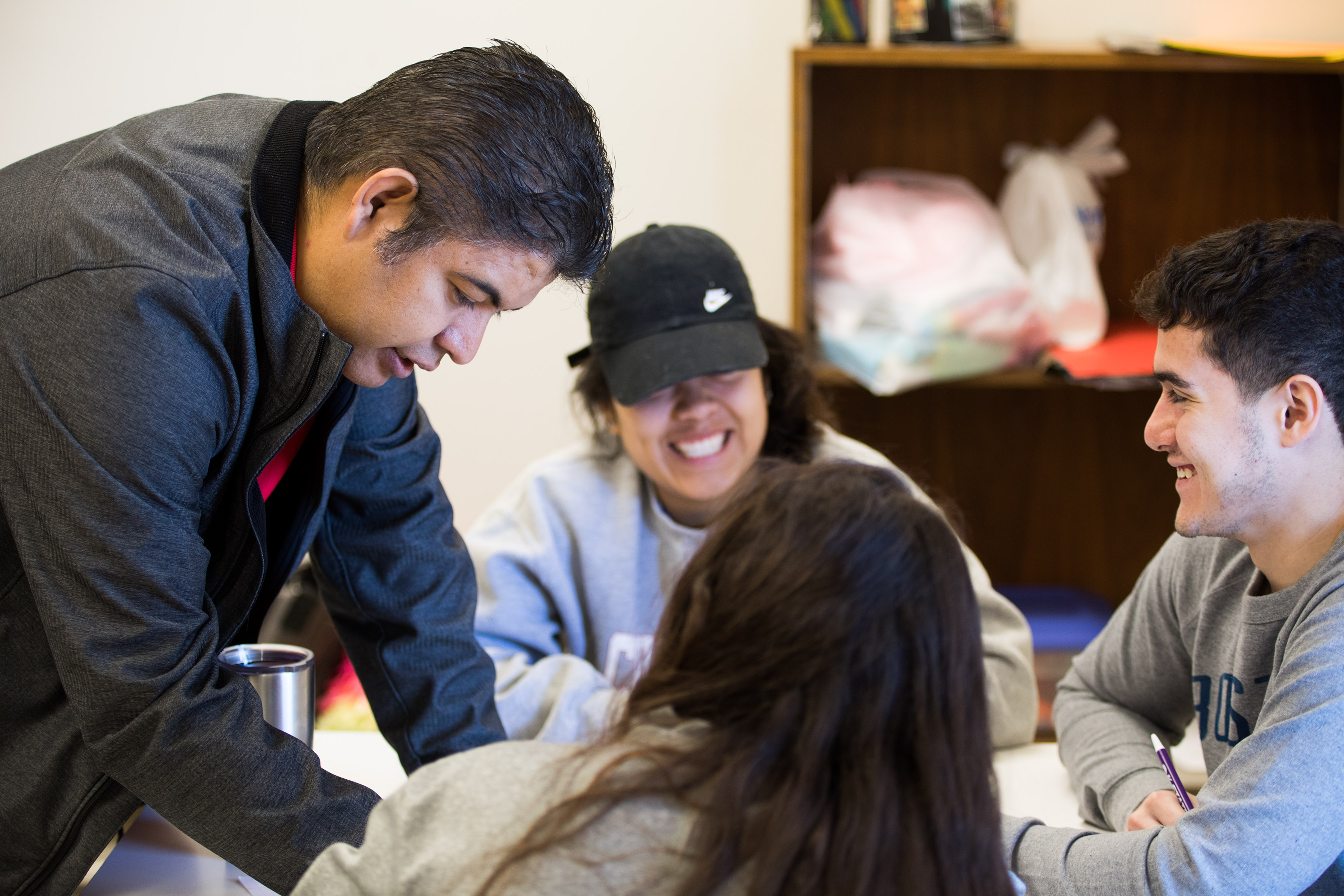 SARC Director Jorge Estrella works with students in the International Club