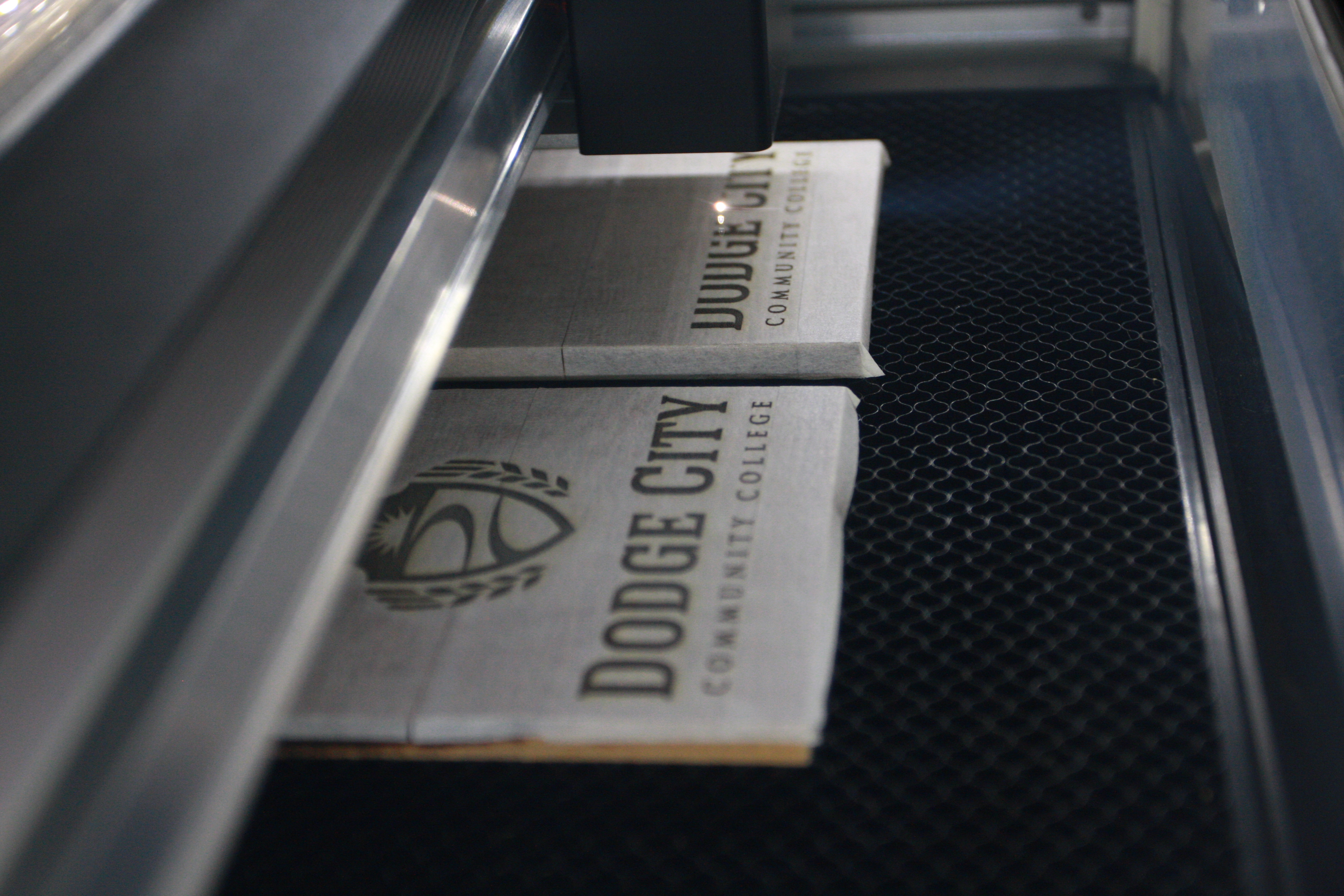 The Glowforge engraving wood tiles with the new DC3 academic logo