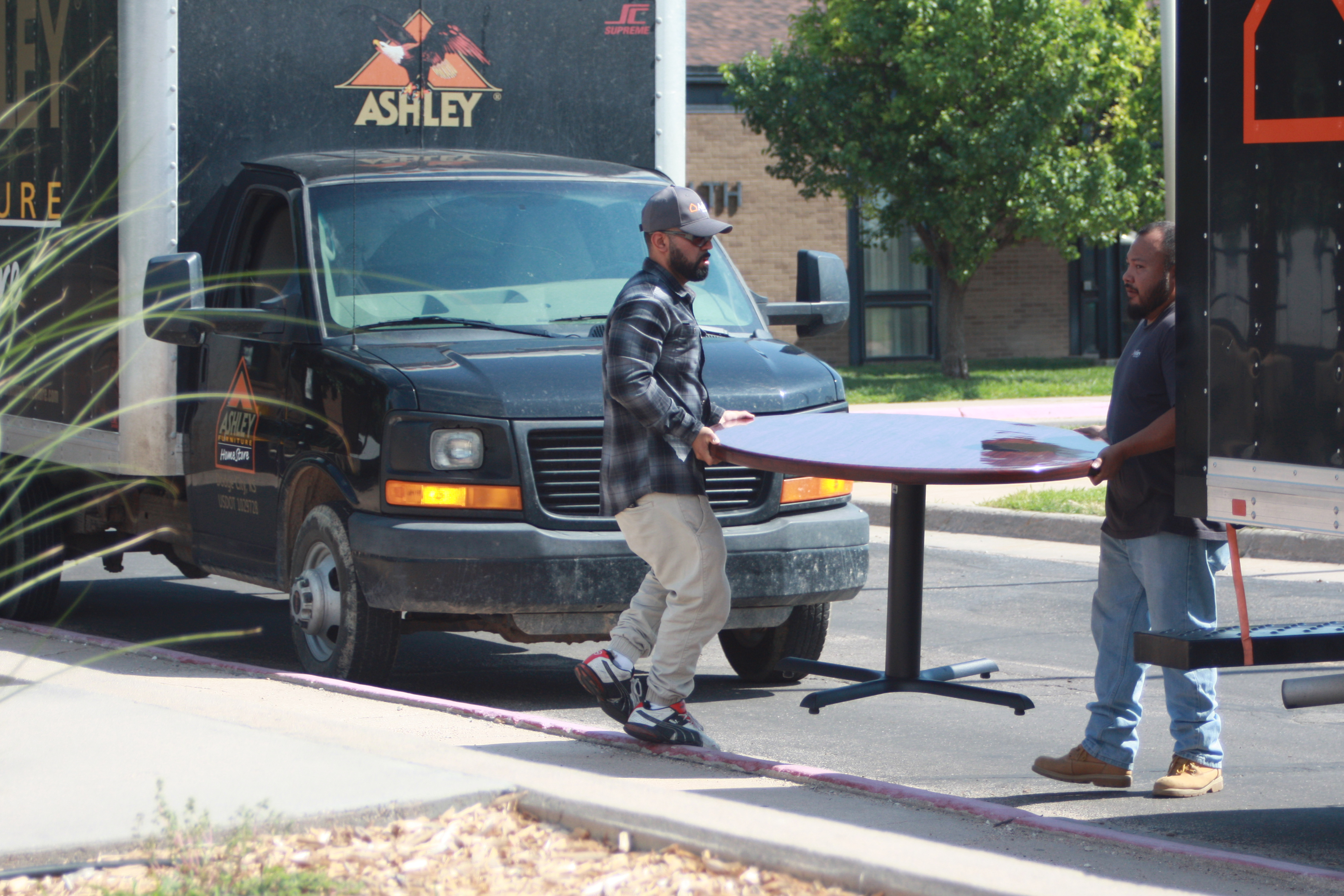 Employees of Ashley Furniture HomeStore carrying at table onto campus