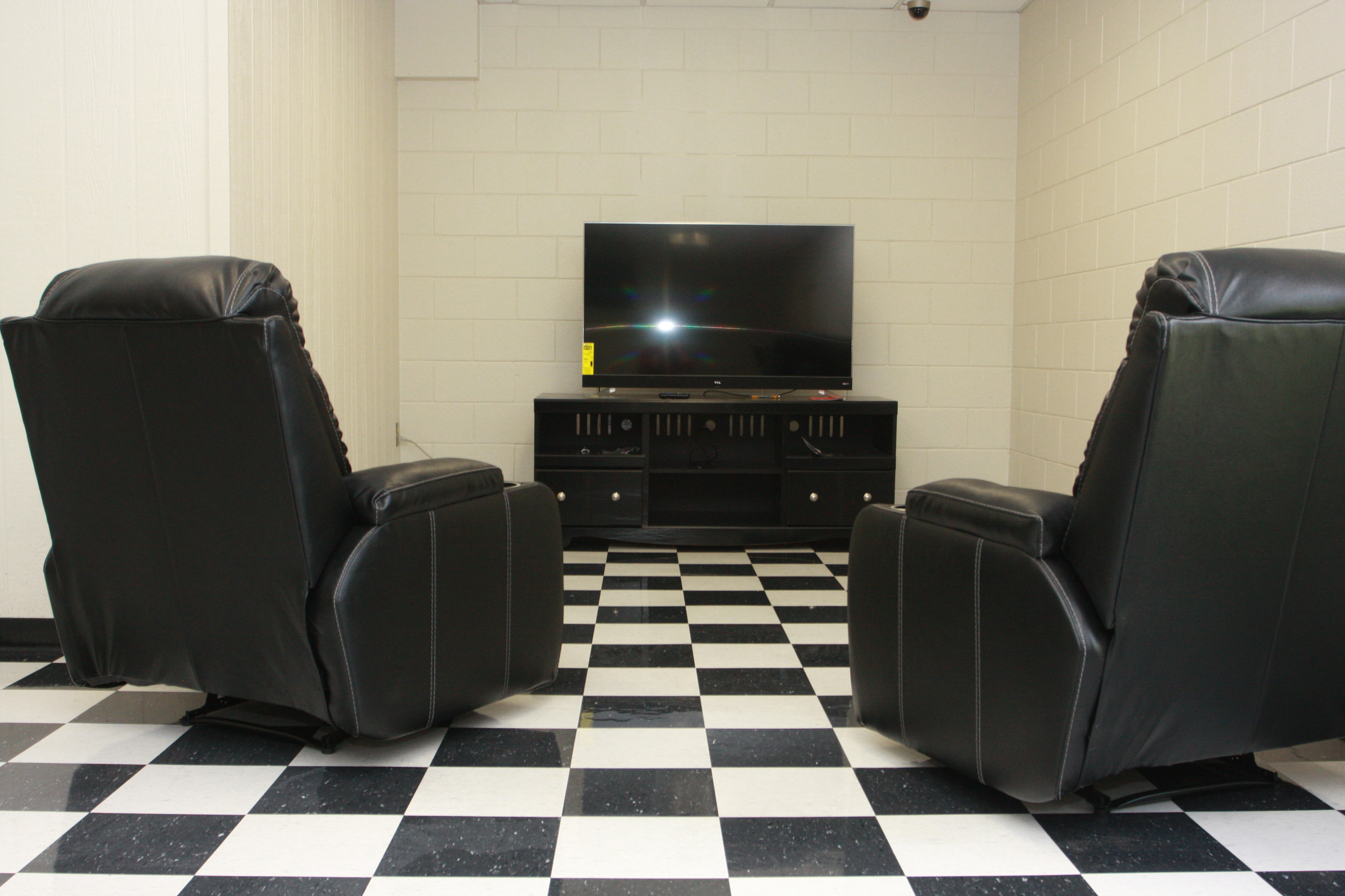 New leather recliners facing an entertainment center with LCD television in the recreation area of the Conq Corral