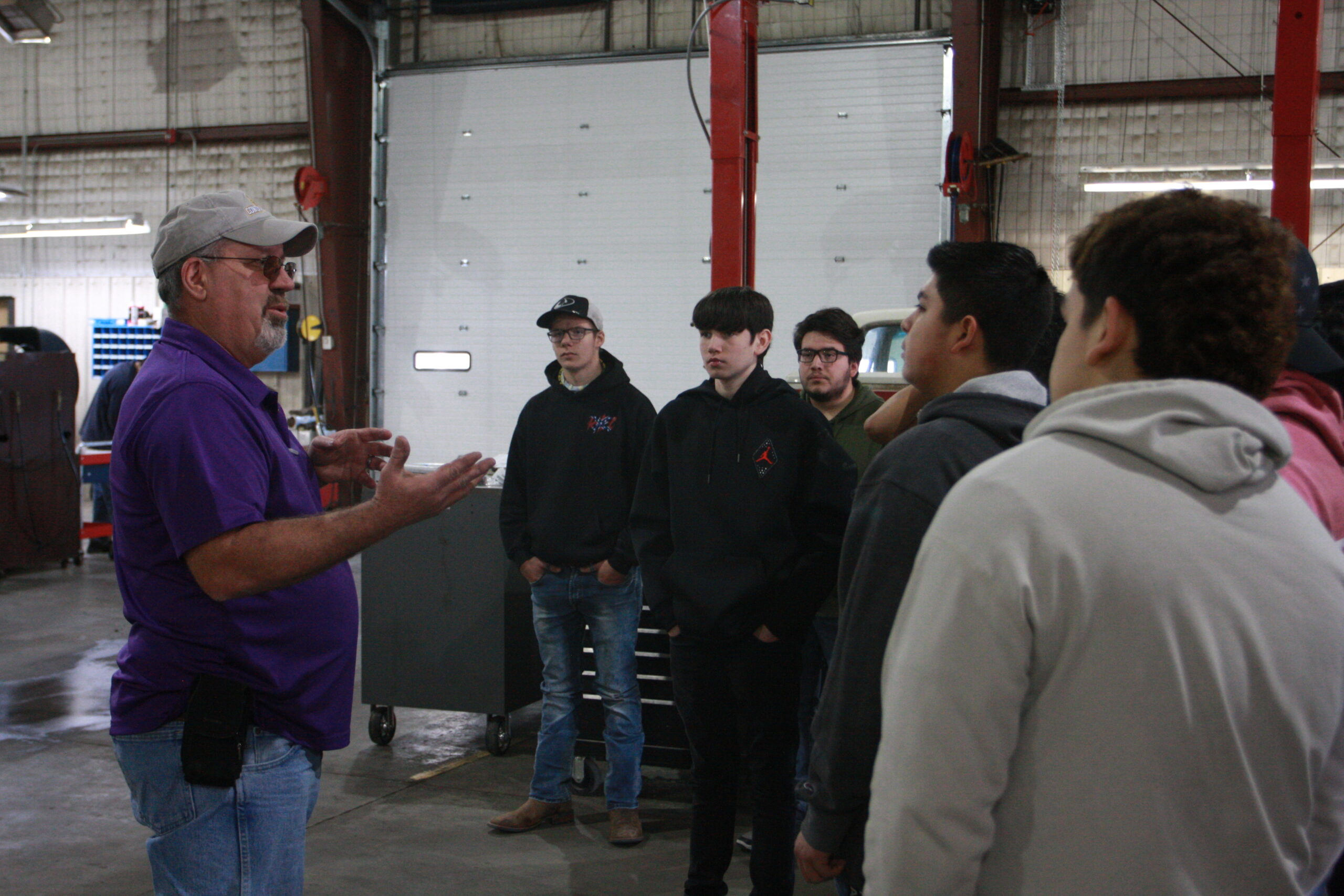 Students from Dodge City High School listening to Jeff Cole,  professor of diesel technology on ag & diesel day