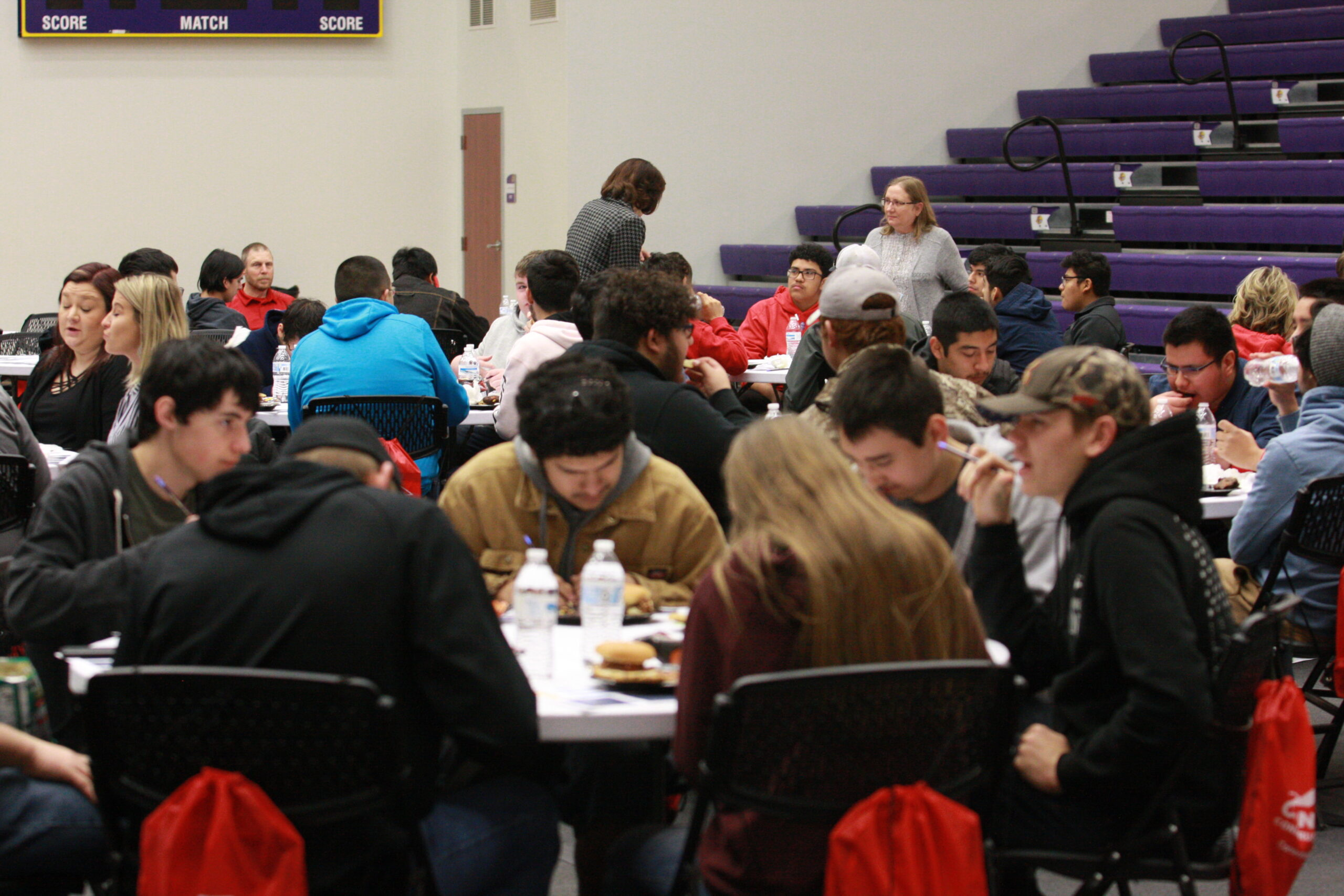 High school students completing comment cards and eating lunch at the DC3 student activity center during construction day