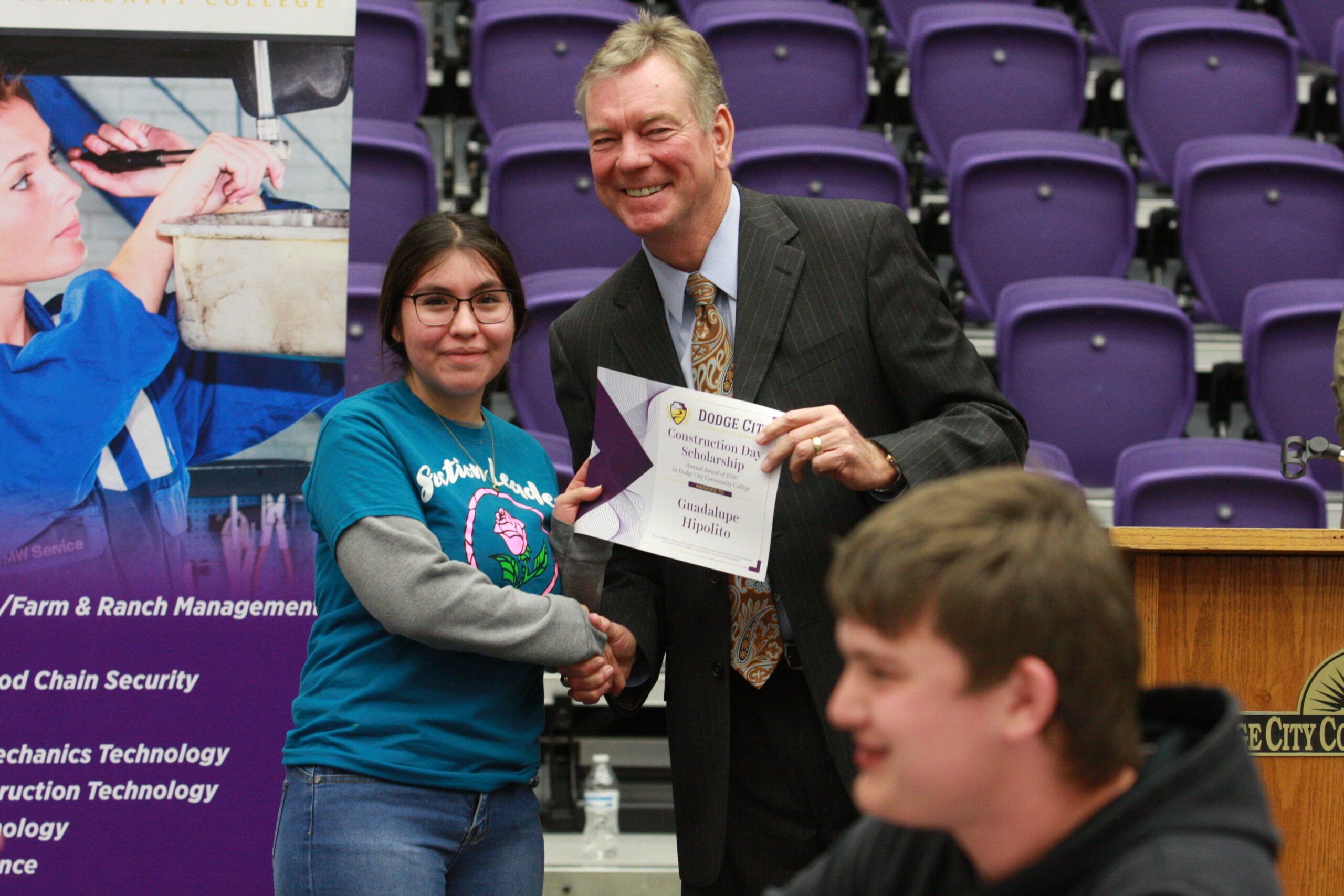 Dr. Harold Nolte, president presenting scholarship to a high school student Guadalupe Hipolito during construction day