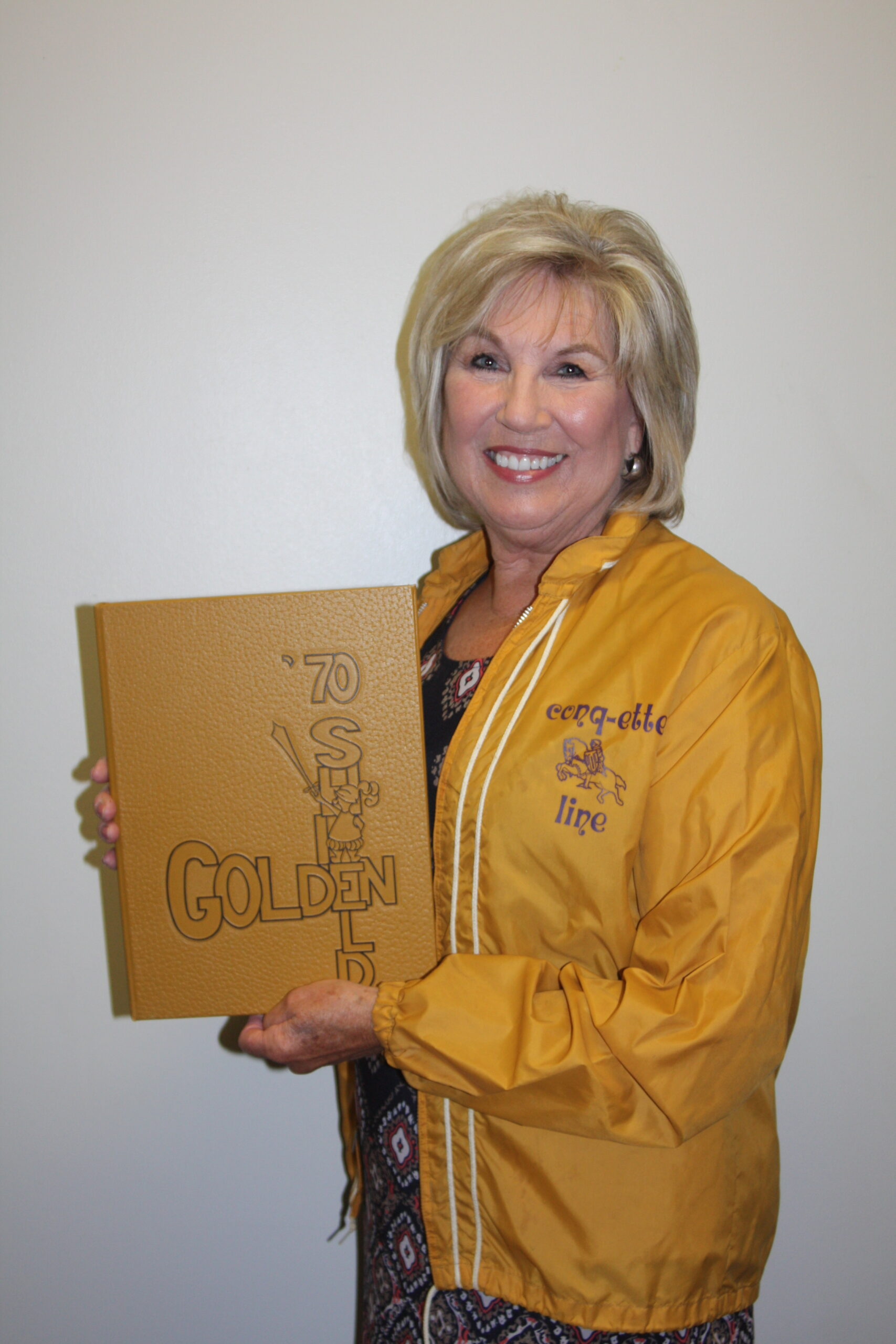 DC3 Board of Trustee, Kathy Ramsour poses with the Golden Shield yearbook and Conquette jacket