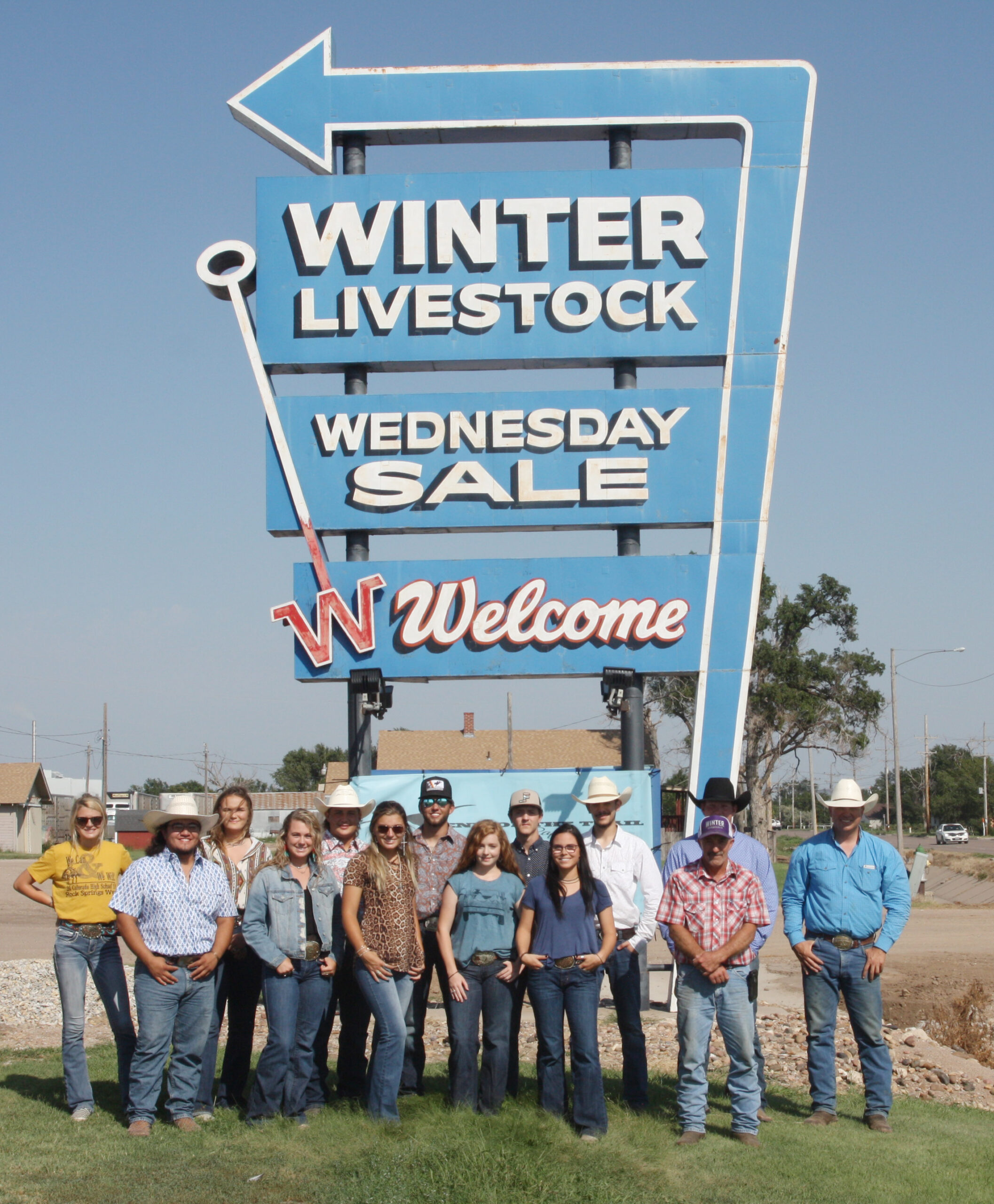DC3 rodeo team poses with their coach, Gabe Burrows and members of Winter Livestock in front of the Winter Livestock sign
