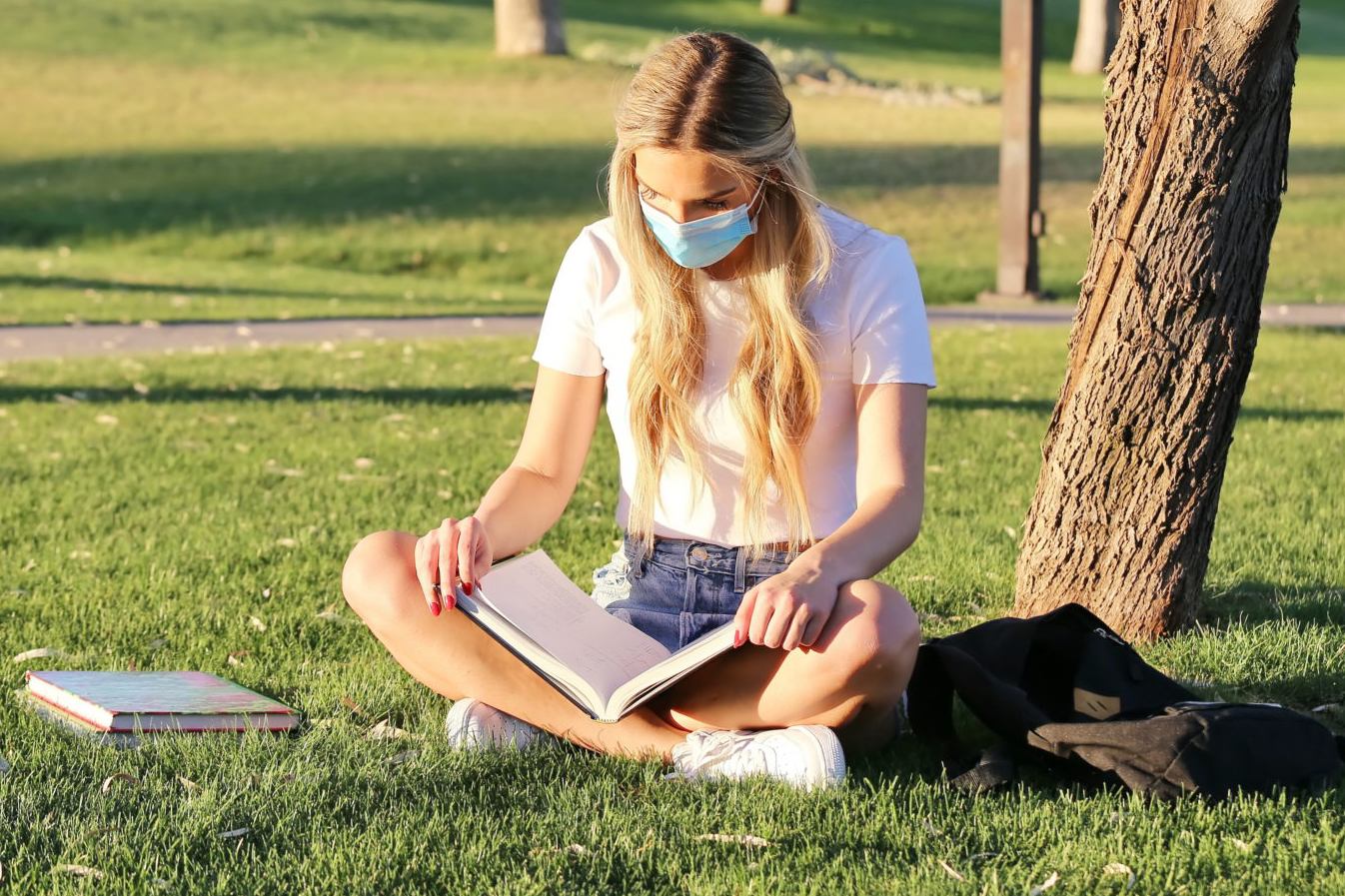 Student outside on campus wearing a mask while reading