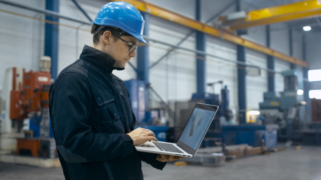 Man in shop working on laptop while wearing a hardhat