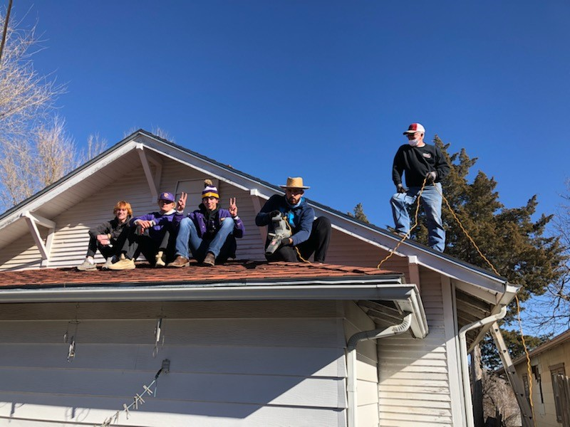 DC3 Baseball team and volunteers cleaning gutters from a rooftop during the RSVP Annual Clean-Up Day
