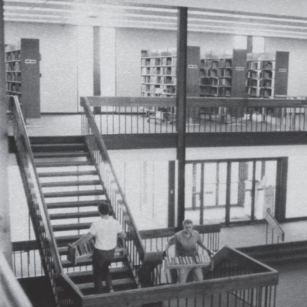 Students carrying books laden with books to the stacks upstairs in the library of the new campus