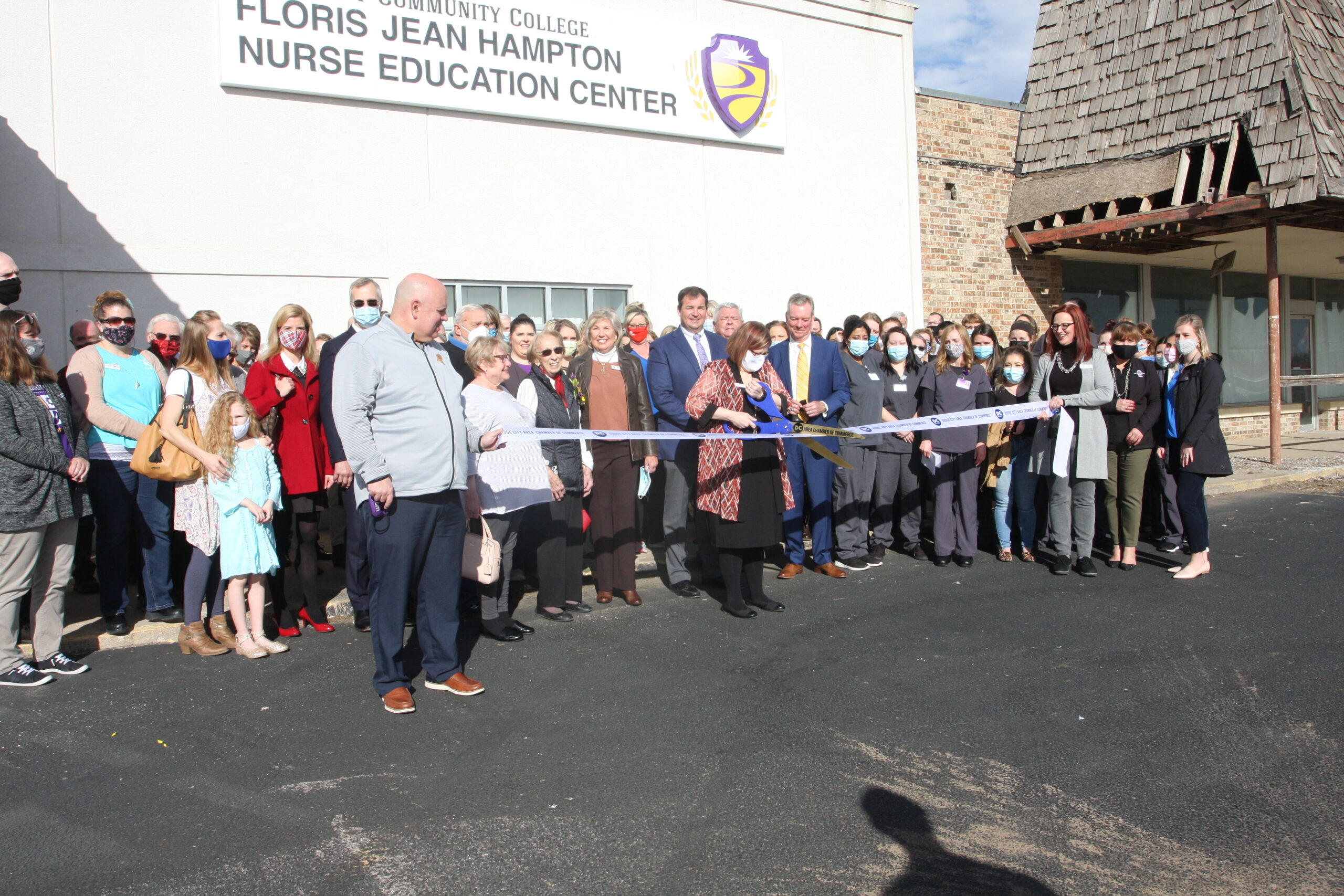 A group of college personnel, family and community members gather for a ribbon cutting outside of the Floris Jean Hampton Nurse Education Center